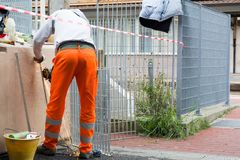 Trabajador que usa una amoladora orbital en la naranja que lleva superficial de acero imagen de archivo libre de regalías