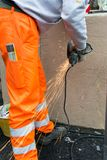 Trabajador que usa una amoladora orbital en la naranja que lleva superficial de acero imagen de archivo