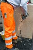 Trabajador que usa una amoladora orbital en la naranja que lleva superficial de acero imágenes de archivo libres de regalías