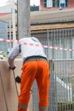 Trabajador que usa una amoladora orbital en la naranja que lleva superficial de acero foto de archivo libre de regalías