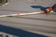 Trabajador que usa una espátula de madera para el cemento después de verter el hormigón preparado fotos de archivo