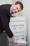 Trabajador que usa una máquina de la copia en una oficina Fotos de archivo libres de regalías