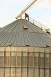 Trabajador rural del grano encima del silo del metal Imagen de archivo