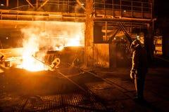 Trabajador siderúrgico al verter el titanio líquido del horno de arco fotografía de archivo libre de regalías