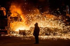 Trabajador siderúrgico cerca de un horno con las chispas Imagenes de archivo