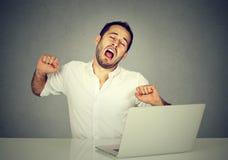 Trabajador soñoliento con el ordenador portátil que bosteza imagenes de archivo