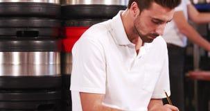 Trabajador sonriente de la cervecería que toma notas sobre el tablero almacen de metraje de vídeo