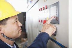 Trabajador sonriente que comprueba controles en una planta de gas, Pekín, China fotos de archivo