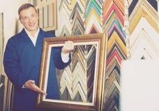 Trabajador sonriente que lleva a cabo moldear que enmarca de la imagen de madera Fotografía de archivo libre de regalías