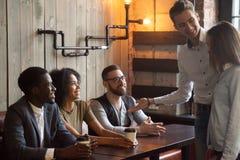 Trabajador sonriente que presenta al nuevo empleado a los colegas durante el caf imagen de archivo