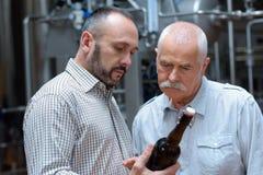 Trabajador y cervecero que celebran la botella de cerveza en cajón en la cervecería imágenes de archivo libres de regalías