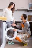 Trabajador y cliente cerca de la lavadora Imágenes de archivo libres de regalías