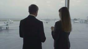 Trabajador y hombre de negocios del aeropuerto en el aeropuerto cerca de la ventana almacen de metraje de vídeo