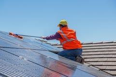 Trabajador y los paneles solares Foto de archivo