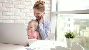 Trabajadora con el teléfono de discurso del bebé Mamá del negocio con el niño almacen de metraje de vídeo