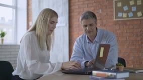 Trabajadora que mecanografía en un ordenador portátil y que muestra el resultado a un socio los hombres de negocios sacuden las m metrajes