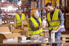 Trabajadores agradables del almacén que ponen etiquetas imagen de archivo libre de regalías