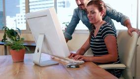 Trabajadores casuales del negocio que miran el ordenador almacen de video