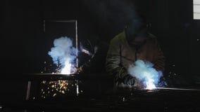 Trabajadores con el metal de soldadura de la máscara protectora metrajes