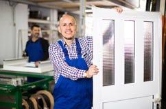 Trabajadores con las ventanas y las puertas del PVC Imágenes de archivo libres de regalías