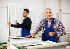 Trabajadores con las ventanas y las puertas del PVC Imagen de archivo libre de regalías