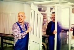 Trabajadores con las ventanas y las puertas del PVC imagen de archivo