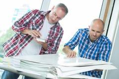 Trabajadores con los papeles de la pila Foto de archivo libre de regalías