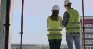 Trabajadores constructivos que trabajan en el emplazamiento de la obra, constructores que miran en el modelo, visi?n trasera, esp metrajes