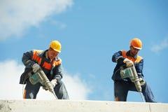 Trabajadores de construcción con el perforador Imágenes de archivo libres de regalías
