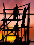 Trabajadores de construcción contra puesta del sol colorida Imagen de archivo libre de regalías