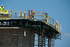 Trabajadores de construcción en el andamio Imágenes de archivo libres de regalías