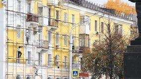 Trabajadores de construcción en el andamio que repara el edificio soviético clásico del estilo del cinco-piso metrajes