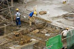 Trabajadores de construcción en el edificio alto Foto de archivo