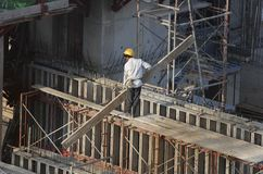 Trabajadores de construcción en el edificio alto Imágenes de archivo libres de regalías
