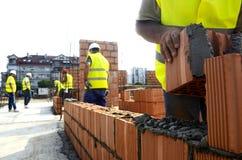 Trabajadores de construcción en el emplazamiento de la obra fotos de archivo libres de regalías