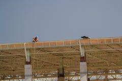 Trabajadores de construcción en el tejado del edificio imagen de archivo