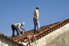 Trabajadores de construcción en el trabajo sobre un tejado, Portugal Imagenes de archivo