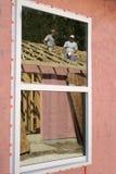 Trabajadores de construcción en la reflexión de la ventana Fotografía de archivo libre de regalías