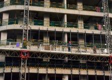 Trabajadores de construcción en plataforma móvil de la construcción hidráulica Reparación de la fachada del edificio Edificio de  fotografía de archivo libre de regalías