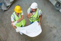 Trabajadores de construcción envueltos para arriba en la discusión Foto de archivo libre de regalías