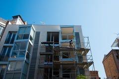 Trabajadores de construcción jovenes en el edificio del andamio en día soleado con el cielo azul claro imagenes de archivo