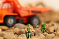 Trabajadores de construcción miniatura en la grava con el camión de volquete Imágenes de archivo libres de regalías