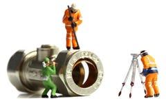 Trabajadores de construcción miniatura que sondean la válvula Foto de archivo libre de regalías