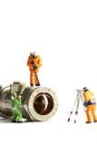 Trabajadores de construcción miniatura que sondean la válvula Foto de archivo