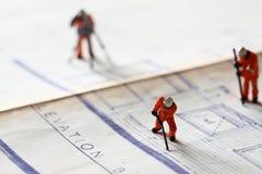 Trabajadores de construcción modelo que construyen los planes D Imágenes de archivo libres de regalías