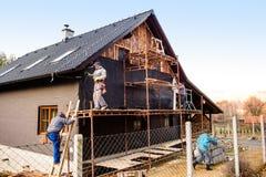 Trabajadores de construcción que aíslan termalmente la casa con las lanas de cristal Imagen de archivo