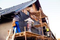 Trabajadores de construcción que aíslan termalmente la casa con las lanas de cristal Imagenes de archivo