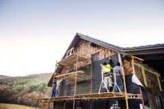 Trabajadores de construcción que aíslan termalmente la casa con las lanas de cristal y la hoja Foto de archivo libre de regalías