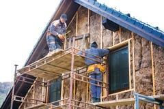 Trabajadores de construcción que aíslan termalmente la fachada de la casa con las lanas de cristal Imágenes de archivo libres de regalías