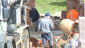 Trabajadores de construcción que alisan el piso concreto almacen de metraje de vídeo
